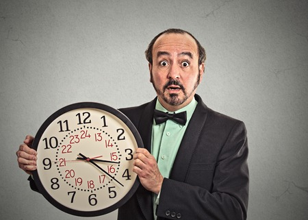 portrait surprised business man in suit holding wall clock isolated grey wall background.