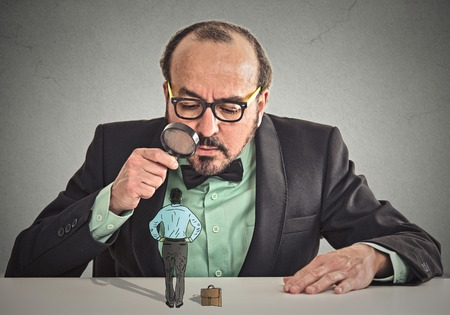 Curious corporate businessman skeptically meeting looking at small employee standing on table through magnifying glass isolated office grey wall background.  Archivio Fotografico