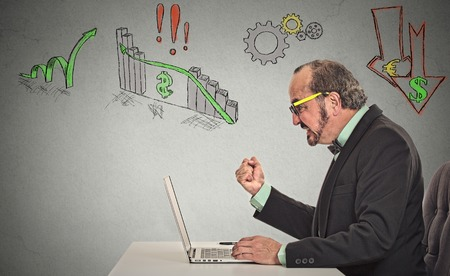 Business man with glasses working on computer upset anticipation of financial crisis bad poor economy isolated grey wall background.  photo