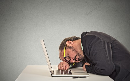 deprived: Businessman sleeping on a laptop on grey office wall background