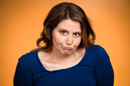 aggravated: Closeup portrait displeased, pissed off, angry, grumpy middle aged woman with bad attitude looking at you isolated orange background.  Stock Photo