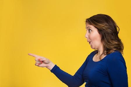 desprecio: Vista lateral del retrato del perfil emocionado informal femenina señalando copia espacio aislado más de fondo amarillo.