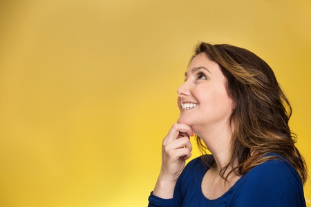 Side view profile portrait thoughtful happy woman smiling looking up daydreaming isolated over yellow background. Positive human face expressions, emotions, feelings, perception Stock Photo