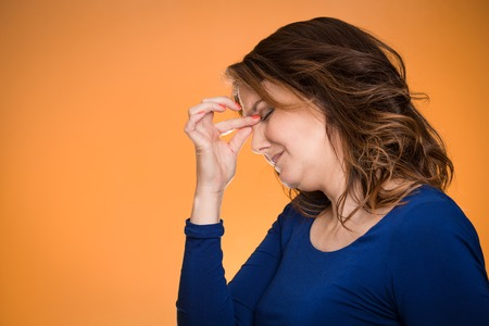 pms: Portrait side view profile of stressed housewife middle aged woman with headache isolated on orange background.