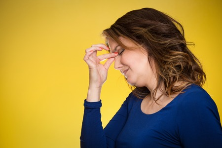 Portrait side view profile of stressed housewife middle aged woman with headache isolated on yellow background.