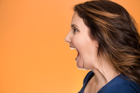 Side view profile portrait beautiful angry woman screaming wide open mouth isolated on orange background.  photo
