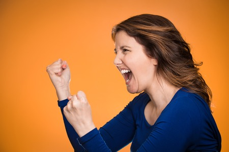 hysterical: Side view profile portrait beautiful angry woman screaming isolated on orange background.