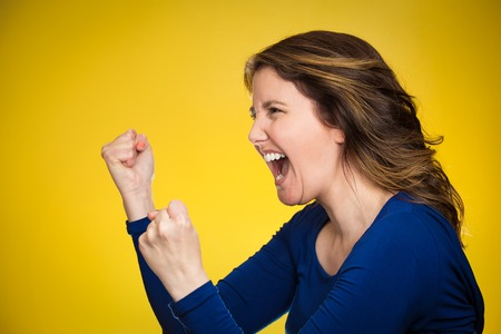 crazy girl: Side view profile portrait beautiful angry woman screaming isolated on yellow background.