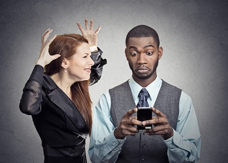 obsession: Attractive woman angry with handsome man who ignores her looking at smart phone reading texting isolated grey wall background.  Stock Photo