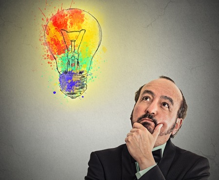 Middle aged business man with thoughtful expression and light bulb over his head looking up thinking isolated grey wall background.  photo
