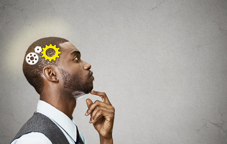 Side view portrait young business man thinking deciding finger on chin looking up gear mechanism over head isolated grey wall background copy space. 스톡 콘텐츠