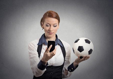 Portrait business woman looking on cell smart phone watching game holding football isolated grey wall background. Positive emotion, face expression. Data plan online gaming. Team leadership concept photo