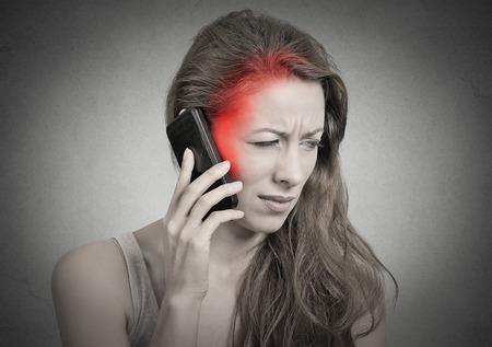 contaminacion acustica: chica en el teléfono con dolor de cabeza. Malestar mujer infeliz, hablando por teléfono aislado fondo de la pared gris. Emoción cara Reacción negativa sentimiento expresión de la vida humana. Celular concepto radiación móvil