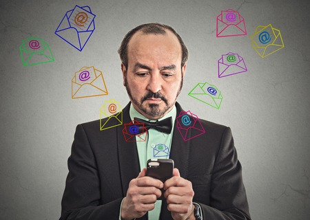 Business man busy sending message email from smartphone email icons coming out flying of mobile phone isolated grey wall background. telecommunications, internet, data plan, 4G, world wide web concept