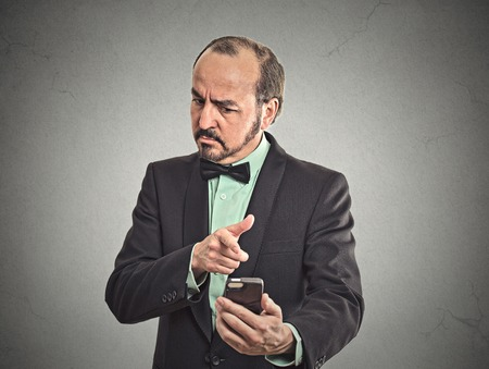 pissed off: Portrait angry middle aged business man guy mad worker pissed off employee while on mobile pointing with finger at smart phone isolated grey wall office background. Negative emotion facial expression