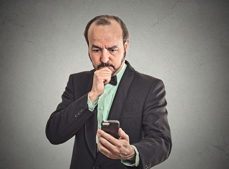 bad planning: Closeup portrait puzzled confused business man looking on smartphone thinking what to reply on received text message texting isolated grey wall background. Human face expression reaction body language Stock Photo