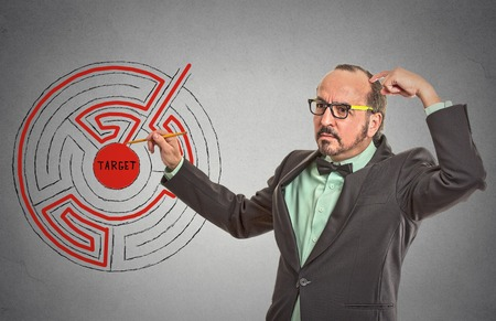 scratching head: Target man labyrinth. Man drawing with pencil red path line through maze to success isolated grey wall office background. leadership guidance idea skills concept. Guy scratching head solving problem