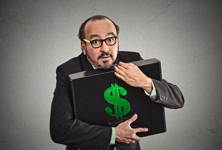 L'avidità di denaro. Holding dell'uomo di affari caso di partecipazione con i dollari ben isolato su sfondo grigio muro. Culto, miser, eccessivo aumento, il concetto di finanza