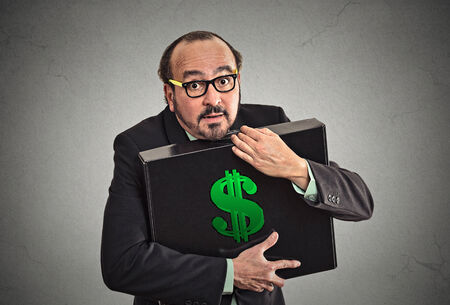 Money greed. Business man holding holding case with dollars tightly isolated on grey wall background. Worship, miser, excessive gain, finance concept Stock Photo