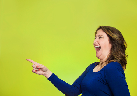 Side view profile portrait middle aged excited happy laughing woman pointing finger at something someone isolated green background with copy space. Positive human emotion face expression reaction Stock Photo
