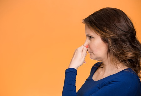 unpleasant smell: Side view profile portrait middle aged woman covers pinches her nose with hand looks with disgust, something stinks bad smell situation isolated orange background. Human face expression body language