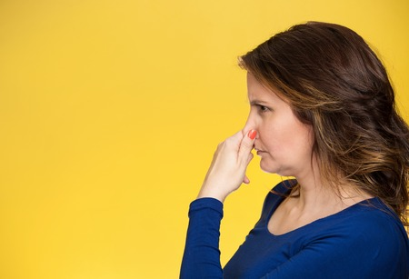 smelly: Side view profile portrait middle aged woman covers pinches her nose with hand looks with disgust, something stinks bad smell situation isolated yellow background. Human face expression body language Stock Photo