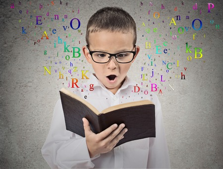 learning: Surprised child reading a book with letters flying away from it isolated on grey wall background. Face expression. Education concept