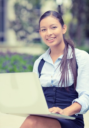 Portrait young happy business woman resting hands on computer laptop keyboard looking at camera isolated outside park with trees background. Positive face expression emotion. Technology concept photo