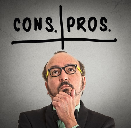 business for the middle: pros and cons, for and against argument concept. Thinking middle aged business man with glasses looking up isolated on grey wall background. Face expression, emotion, feeling, perception, vision Stock Photo