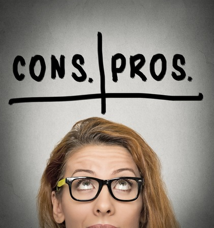 pros: pros and cons, for and against argument concept. Thinking young business woman with glasses looking up isolated on grey wall background. Face expression, emotion, feeling, perception, vision, decision