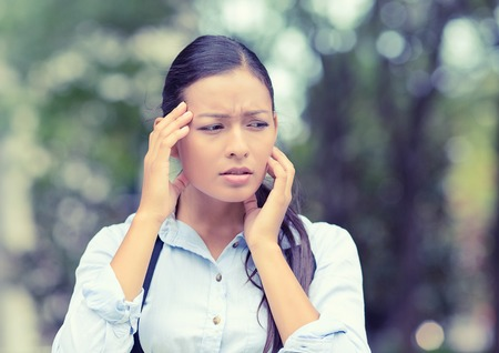 bothered: Stress. Closeup portrait unhappy business woman hands on head bothered by mistake having bad headache isolated outside outdoors background with park trees. Negative human emotion facial expression Stock Photo