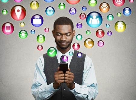 black man browsing: communication technology mobile phone high tech concept. business man using texting on smartphone social media application icons flying out of cellphone isolated grey wall background. 4g data plan Stock Photo