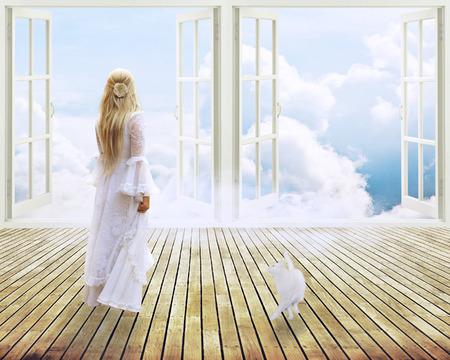 bella ragazza in abito bianco in piedi guardando nella finestra aperta sogni luce del giorno cielo surreale vista sullo skyline. Archivio Fotografico