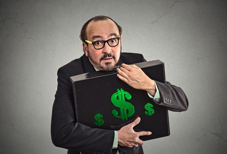 scrooge: Money greed wealth security. Wealthy business man in suit holding holding hugging tight case full with dollars money isolated grey wall background. Worship, miser, excessive gain, finance concept Stock Photo
