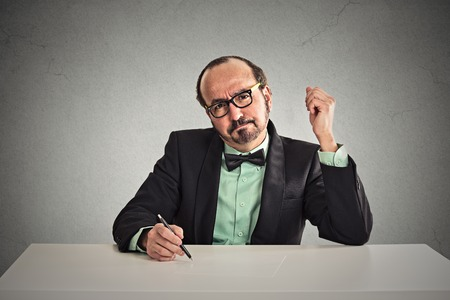 skeptic: Serious middle aged businessman with glasses skeptically looking at you sitting at his desk isolated on office grey wall background. Human face expression, body language, attitude, perception