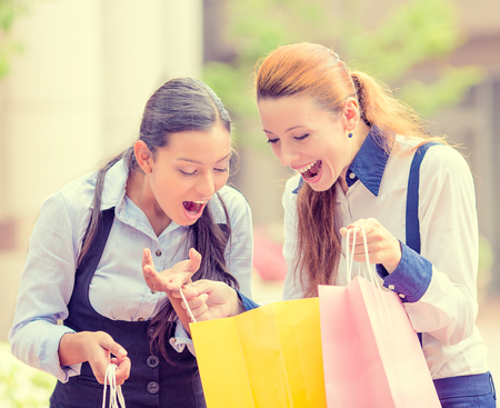 Portrait two happy, laughing young women showing each other what they bought in shopping mall, isolated outdoor street background. Positive human emotions, feeling, face expressions, lifestyle photo