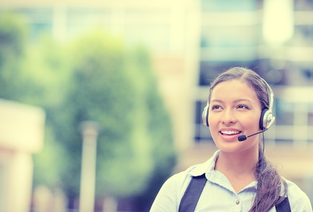 Closeup portrait smiling young female customer service representative, call center agent, support staff, operator with phone headset isolated on background with trees, city buildings. Face expression photo