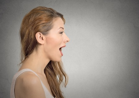 monologue: Closeup side view profile portrait woman talking with sound coming out of her open mouth isolated grey wall background. Human face expression emotions. Communication, information, intelligence concept