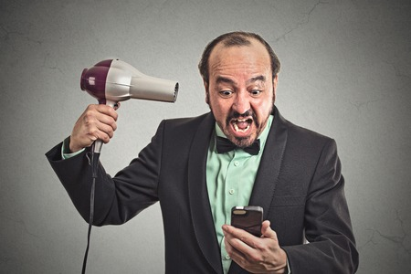 thinning: Closeup portrait angry business man screaming looking on smartphone holding hairdryer something blows his mind isolated grey background. Face expression emotion. Stressful life of corporate executive