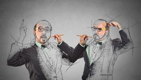 Crea usted, su futuro destino, imagen, concepto de carrera. Hombre de mediana edad haciendo un dibujo, boceto de sí mismo en la pared de fondo gris. Expresiones faciales Humanos, la determinación, la creatividad imaginación