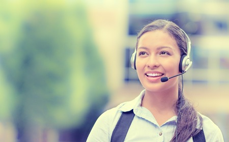support agent: Closeup portrait smiling young female customer service representative, call center agent, support staff, operator with phone headset isolated on background with trees, city buildings. Face expression Stock Photo