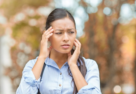bothered: Stress. Closeup portrait unhappy business woman hands on head bothered by mistake having bad headache isolated outside outdoors background with autumn trees. Negative human emotion facial expression Stock Photo
