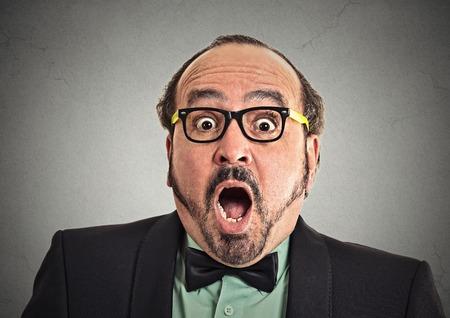 asombro: Sorpresa hombre asombrado. Retrato del primer hombre que parece sorprendida en plena incredulidad amplia boca abierta aislados fondo gris de la pared. Positivo emoción humana expresión facial lenguaje corporal. Individuo divertido Foto de archivo