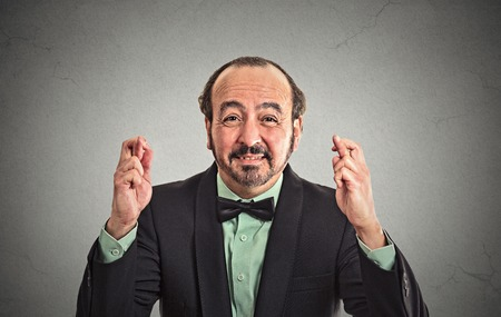 business for the middle: Closeup portrait middle aged funny guy business man crossing fingers wishing hoping for best miracle isolated black grey wall background. Positive human emotion facial expression feeling attitude Stock Photo