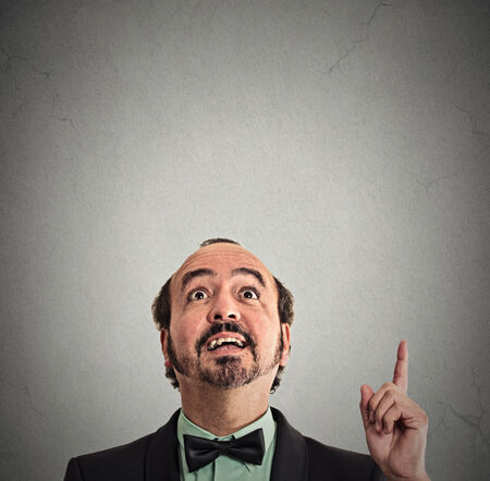 aha: Portrait middle aged man has idea pointing with finger looking up isolated grey wall background with copy space above head. Excited businessman solved problem. Face expression body language perception