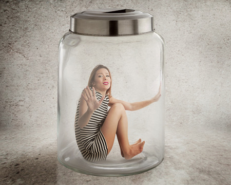 confined space: Lack, violation of human rights liberty. Young lonely woman sitting in glass jar isolated grey wall background. Suppression of freedom, restrain, employee working conditions, life limitation concept
