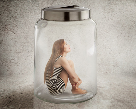 Lack, violation of human rights liberty. Young lonely woman sitting in glass jar isolated grey wall background. Suppression of freedom, restrain, employee working conditions, life limitation concept