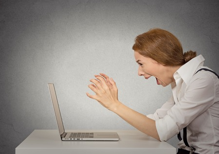 anger management: Angry furious businesswoman sitting in front of computer screaming. Negative human emotions, facial expressions, feelings, aggression, anger management issues concept Stock Photo