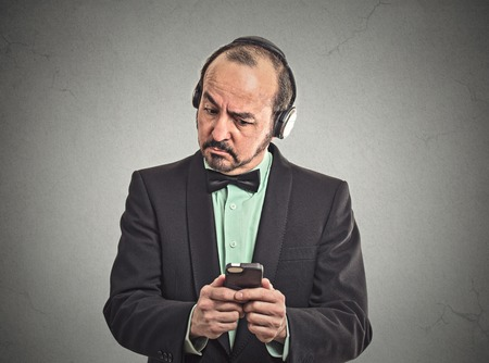 Confused middle aged man listening music with pair of headphones looking at his smartphone surprised. Closeup portrait man reading news on mobile phone isolated grey wall background. Face expression photo