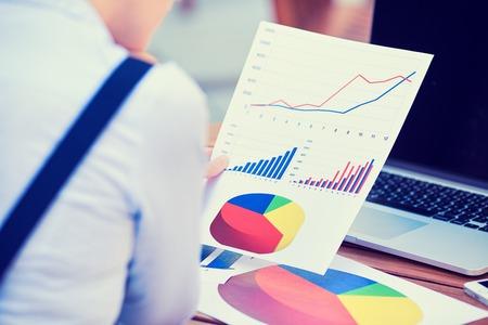 auditor�a: Mujer consultor de inversiones empresa analizar declaraci�n balance informe financiero anual de trabajo con documentos gr�ficos. Mercado de valores, oficina, impuestos, concepto de la educaci�n. Las manos con cartas documentos